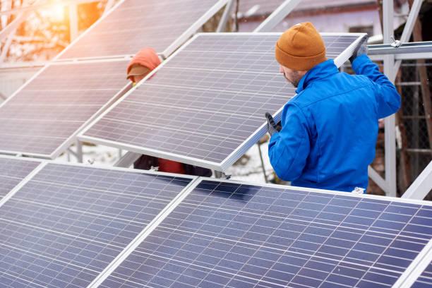 techniker in blauen anzügen, die montage von photovoltaik-solarzellen am dach des modernen hauses. - mondlandefähre stock-fotos und bilder