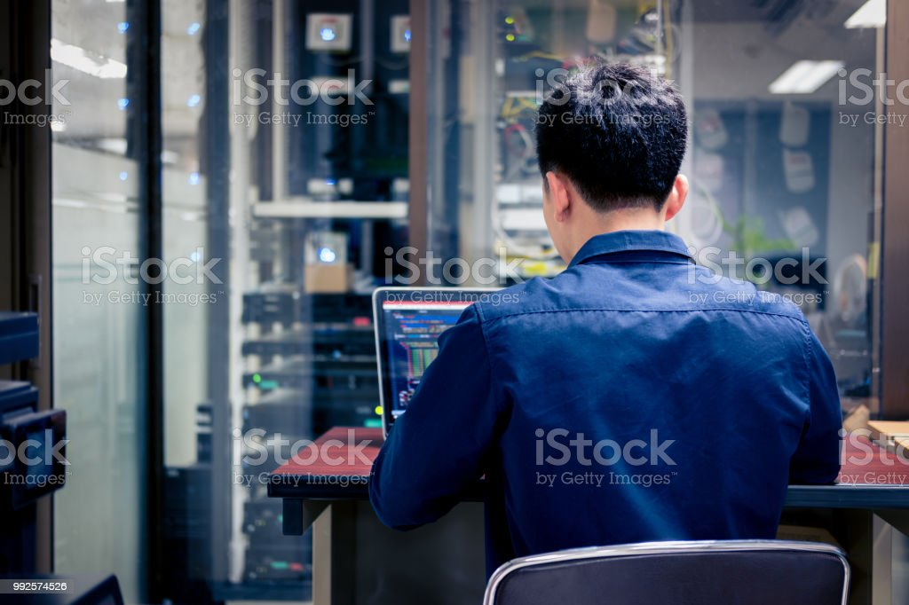 Technicians using laptop while analyzing server in server room stock photo