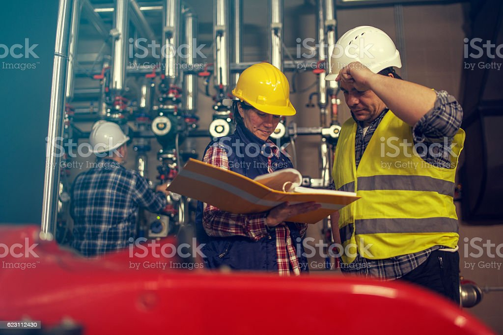 Technicians working in factory or utility stock photo