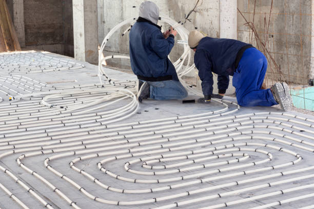 HVAC technicians working on underfloor heating system installation. Close up on water floor heating system interior of a new indoor swimming pool and SPA center. Plumbing pipes. Individual Heating. stock photo