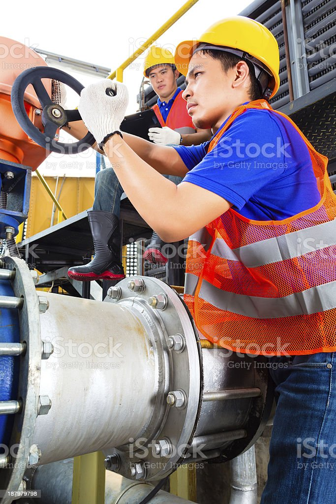 Technicians working on valve in factory or utility royalty-free stock photo