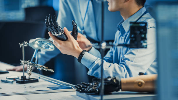 技術補綴ロボットアームは、現代の未来的な機器を備えたハイテク研究所の2人の専門開発エンジニアによってテストされています。パーソナル コンピュータ上のデータを比較します。 - 四肢 ストックフォトと画像