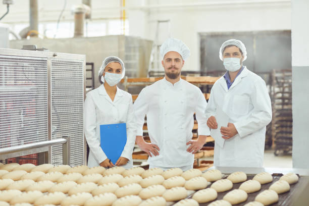 Technologist and baker inspect the bread production line at the bakery stock photo