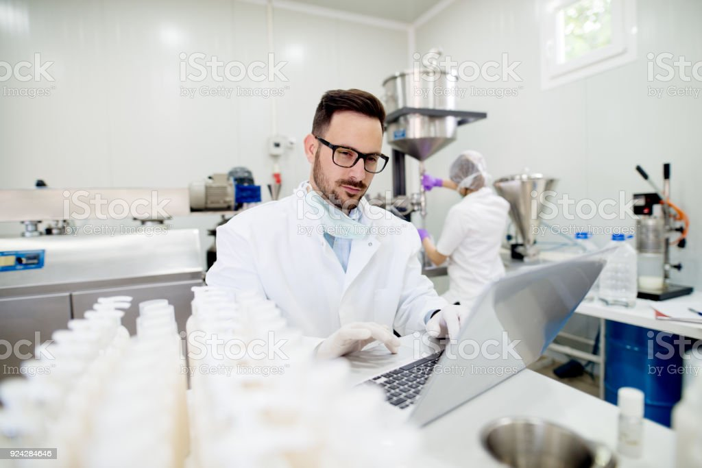 Technologist and machine operator working in cosmetic products factory. Technologist doing analysis on his computer. stock photo