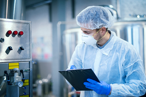Technologist expert in protective uniform with hairnet and mask taking parameters from industrial machine in food production plant.