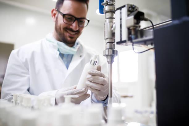 화장품 연구소에 서 있는 동안 액체 비누로 병을 작성 하는 기술자. - 크림 유가공 식품 뉴스 사진 이미지
