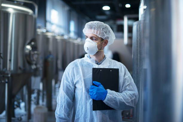 Technologist in protective white suit with hairnet and mask standing in food factory. Technologist at work. hair net stock pictures, royalty-free photos & images