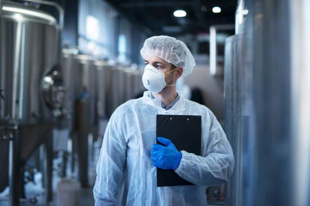 technoloog in beschermende witte pak met hairnet en masker staande in food factory. - kwaliteitscontroleur stockfoto's en -beelden