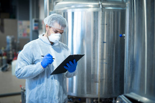 Technologist in white suit. Technologist expert controlling production in pharmaceutical or food processing factory. hair net stock pictures, royalty-free photos & images