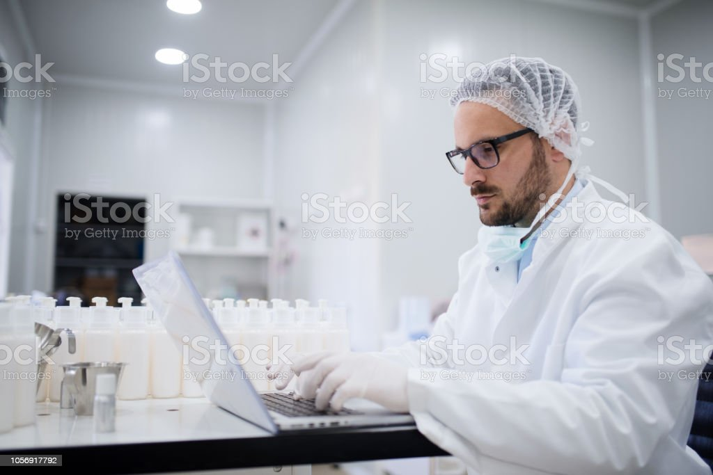 Technologist using laptop for entering data of test results while...