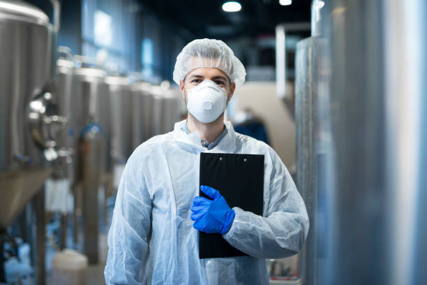 Technologist with protective mask and hairnet standing at factory production line. Food or beverage processing factory. Technologist with protective mask and hairnet standing at factory production line. Food or beverage processing factory. hair net stock pictures, royalty-free photos & images