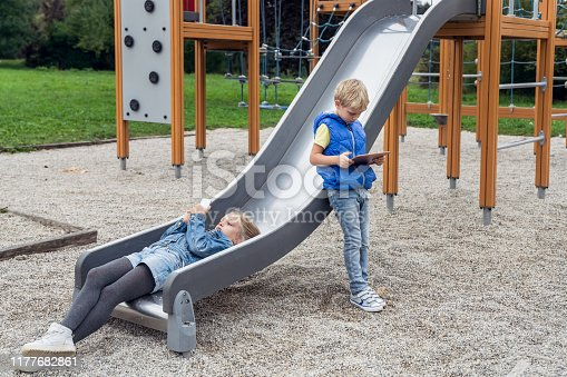 Two kids on playground with digital tablet and smartphone