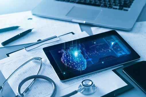 Technology and healthcare, Doctor's cardiologist tablet and heart disease health care analysis data on screen and stethoscope with report heartbeat on table.