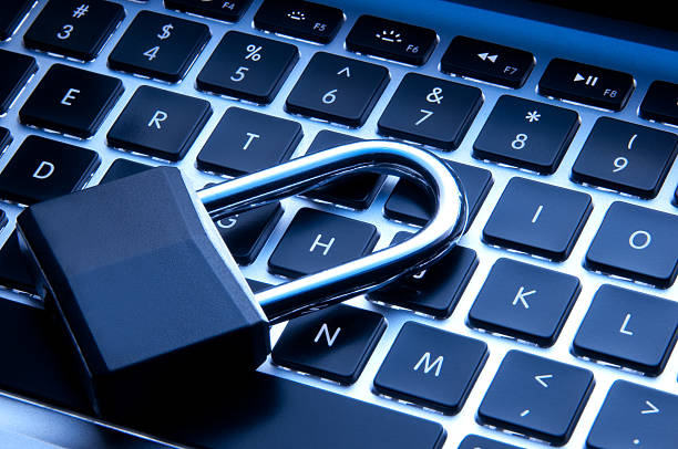 Technology and Security concept Padlock sitting on an illuminated keyboard. identity theft stock pictures, royalty-free photos & images