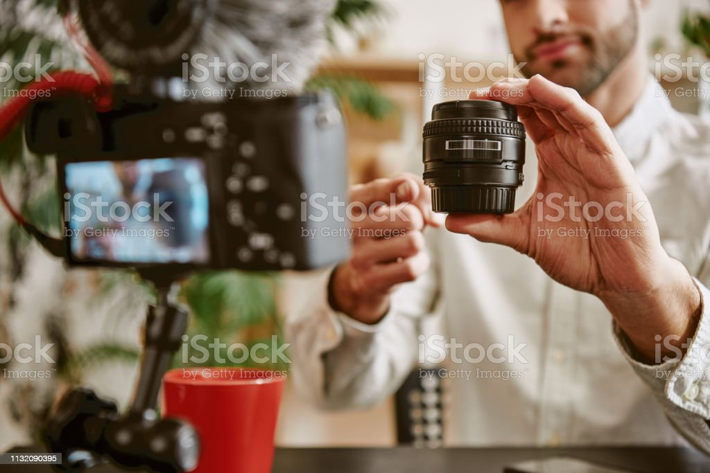Technology blog. Close up photo of blogger's hands showing camera lens online and speaking about its advantages stock photo