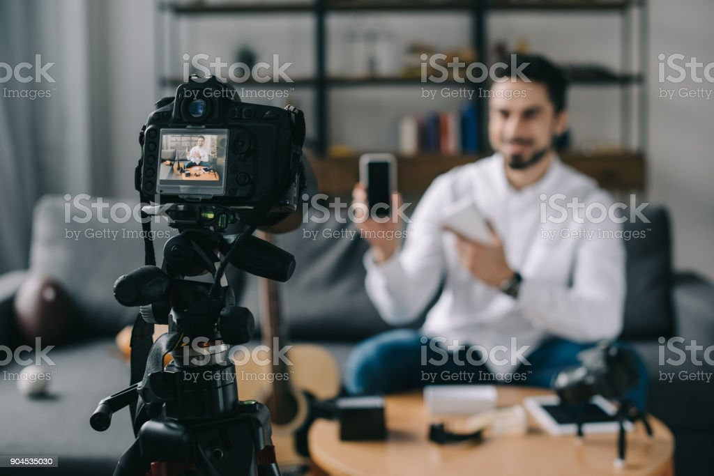 technology blogger pointing on new smartphone with camera on foreground stock photo