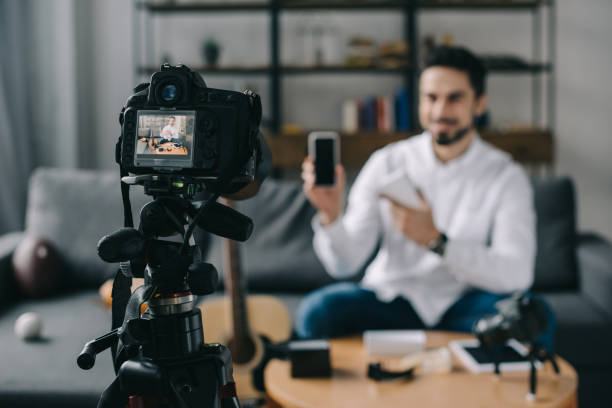 technology blogger pointing on new smartphone with camera on foreground - vlogger stock photos and pictures