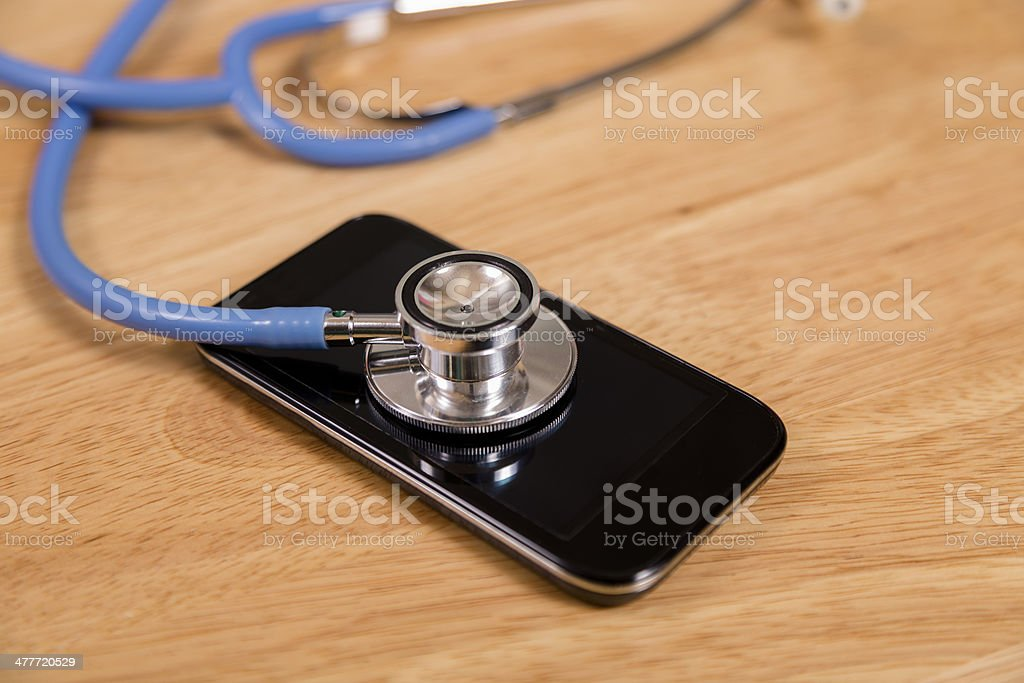 "Technology: Check up for ""sick"" mobile phone. Stethoscope. Stethoscope checks ""vital signs"" of smart phone.  Repair, service, telecommunications, healthcare.  Assistance Stock Photo"