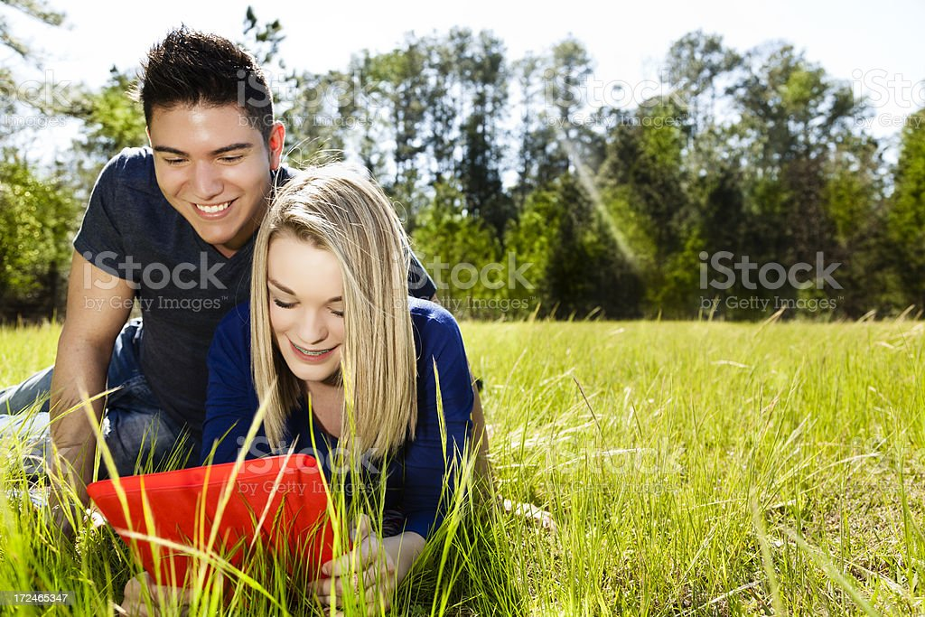 Technology:  Couple outside in grassy park using digital tablet royalty-free stock photo