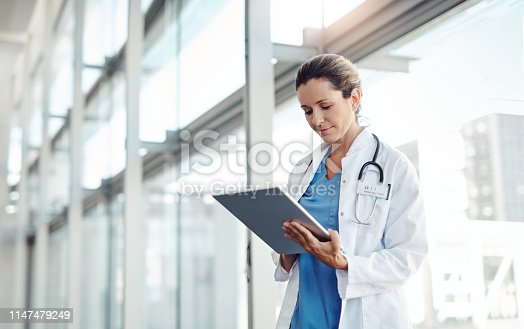 Cropped shot of a female doctor using a digital tablet