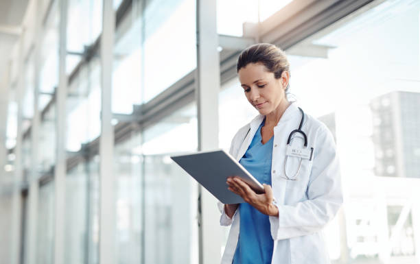 Technology cuts my work in half Cropped shot of a female doctor using a digital tablet ipad stock pictures, royalty-free photos & images