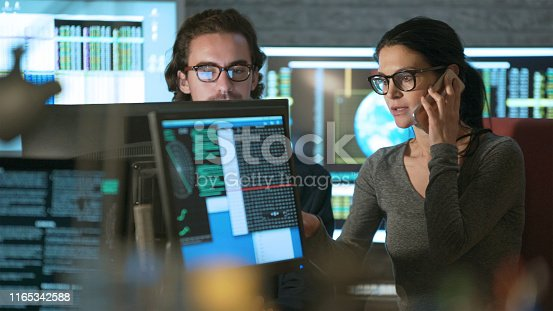 Stock photo of a young man & woman working in an office surrounded by computer monitors displaying moving numerical & scientific data.