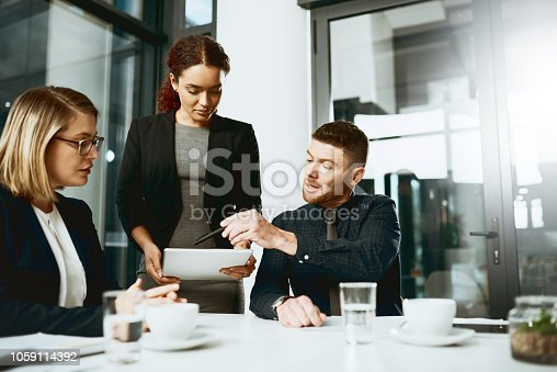 Shot of a group of businesspeople working together on a digital tablet in a boardroom
