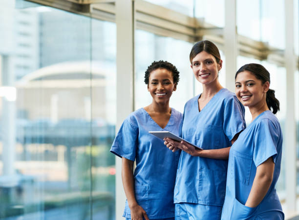 Technology facilitates our day-to-day duties Portrait of a group of medical practitioners using a digital tablet together in a hospital nurses stock pictures, royalty-free photos & images