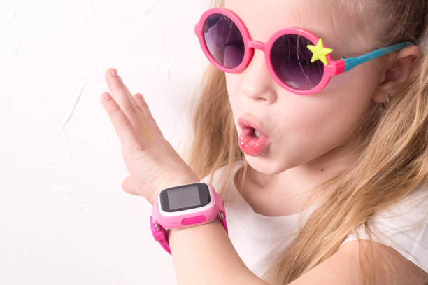 Technology for children: a girl wearing pink glasses uses a smartwatch. stock photo