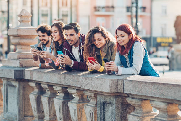 Technology generation Group of young people using smart phones on a bridge digital native stock pictures, royalty-free photos & images