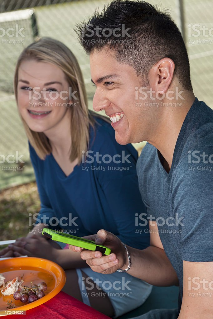 Technology: Happy Teen and young adult at  picnic cell phone royalty-free stock photo