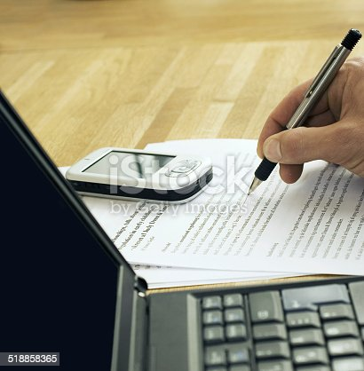 Laptop and cellphone on table with someone writing notes