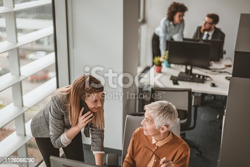 Photo of Casual businesswoman using smartphone, working with mature gray hair colleague next to computer in the office during the day. Brown hair woman with her business woman supervisor. Aged female mentor boss smiling, looking happy for achievement and good online work result of young male intern, senior woman executive leader supervising teaching helping colleague