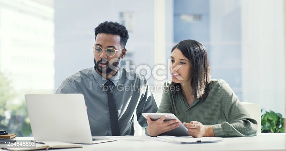 Shot of two businesspeople having a discussion while looking at a laptop
