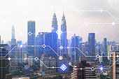 istock Technology hologram over panorama city view of Kuala Lumpur. KL is the largest tech hub in Malaysia, Asia. The concept of developing coding and high-tech science. Double exposure 1304224715