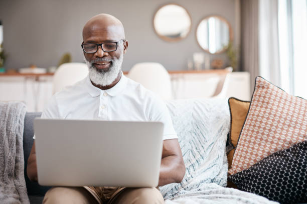 Technology hosts entertainment for all ages Shot of a mature man using a laptop at home man on computer stock pictures, royalty-free photos & images