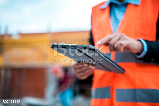 Two architects are using digital tablet on construction site.