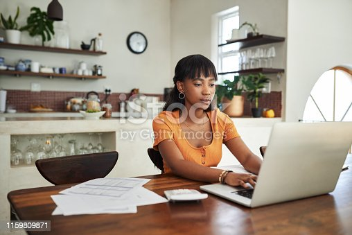 Shot of a young woman sitting with her laptop and paperwork at home