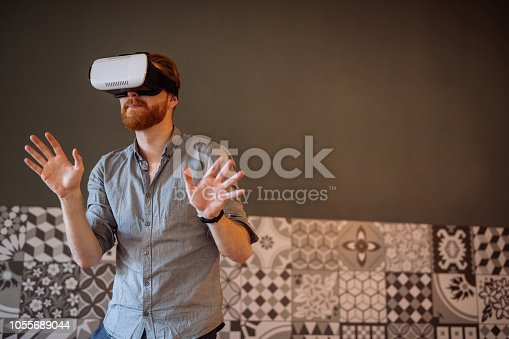 Portrait of an amazed young man wearing virtual reality headset.