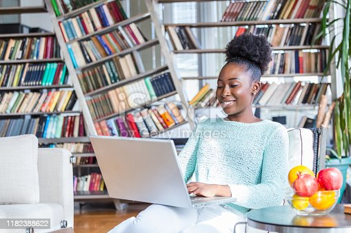 1057767656 istock photo Technology, occupation, freelance and networking concept. Charming young dark skinned female marketing expert working distantly from home office, typing on laptop, making notes and havning coffee 1182388622