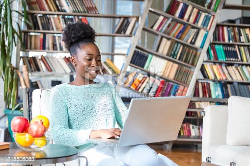 1057767656 istock photo Technology, occupation, freelance and networking concept. Charming young dark skinned female marketing expert working distantly from home office, typing on laptop, making notes and havning coffee 1218508083
