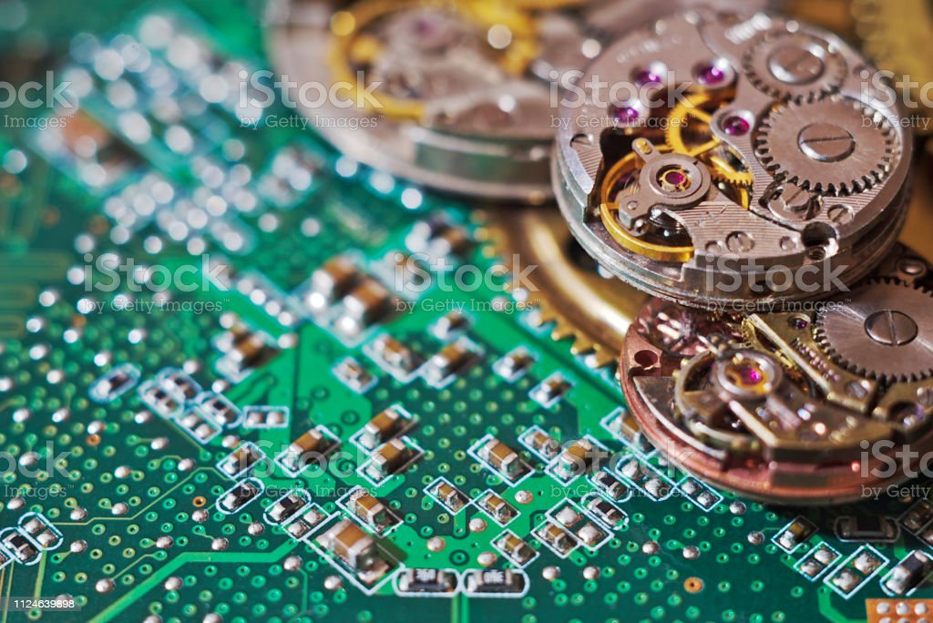Macro shot of a computer circuit board and old wristwatch gears on it.