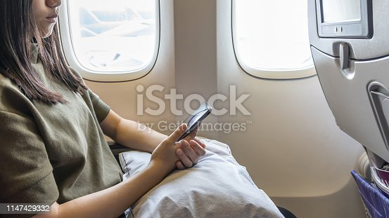 Technology on flight traveling or flying on plane with young girl passenger or woman traveller using mobile smartphone, online app and internet while sitting in airplane seat during journey