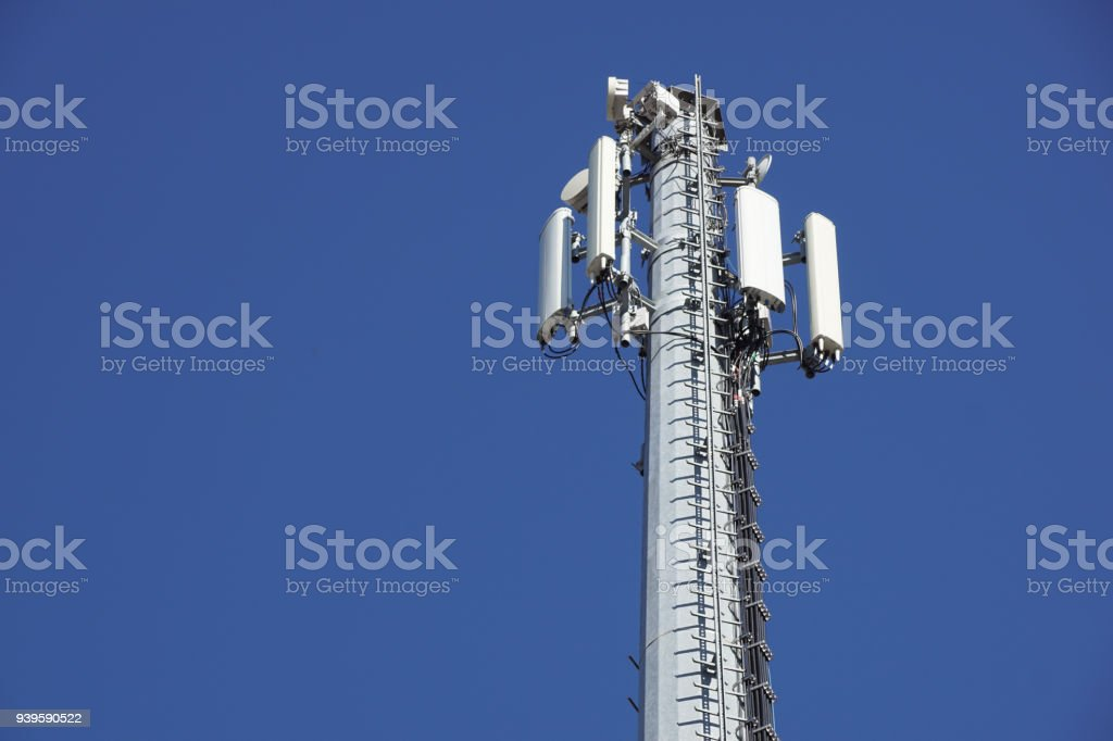 Technology on the top of the telecommunication GSM 4G tower antenna, transmitter , blue sky, white clouds. - foto stock