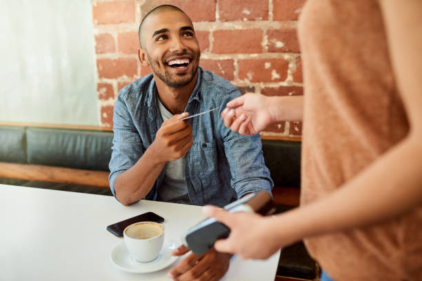 Technology provides the world with convenience Shot of an unrecognizable barista accepting a credit card payment from a customer at a cafe credit card purchase stock pictures, royalty-free photos & images