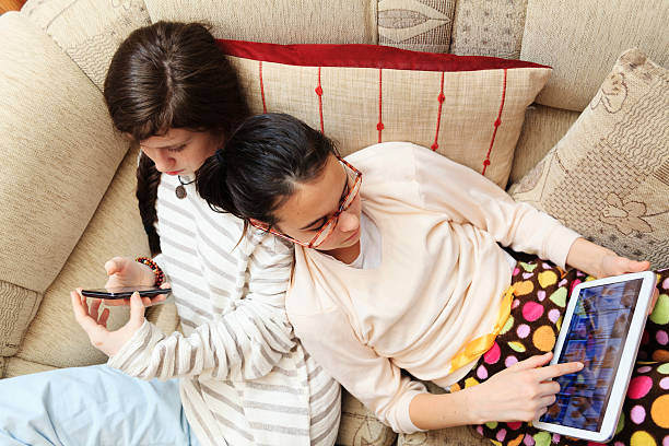 Technology separating kids. Two girls playing with gadgets. stock photo