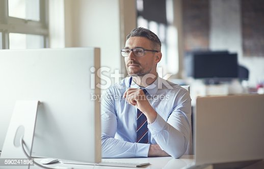 Cropped shot of a businessman sitting by his computer in his office