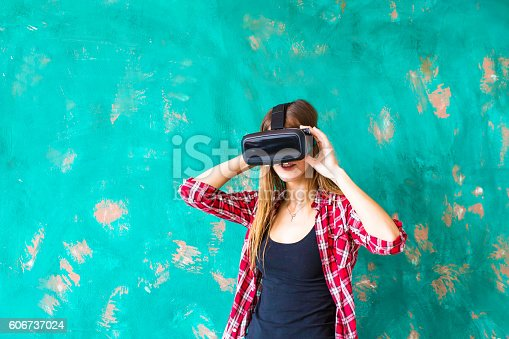 technology, virtual reality, entertainment and people concept - happy young woman with virtual reality headset or 3d glasses and headphones over gray background