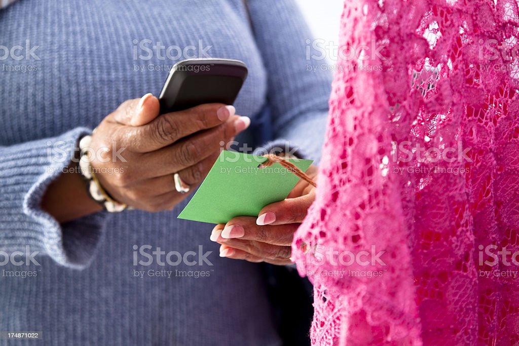 Technology:  Woman reading price tag code with cell phone royalty-free stock photo