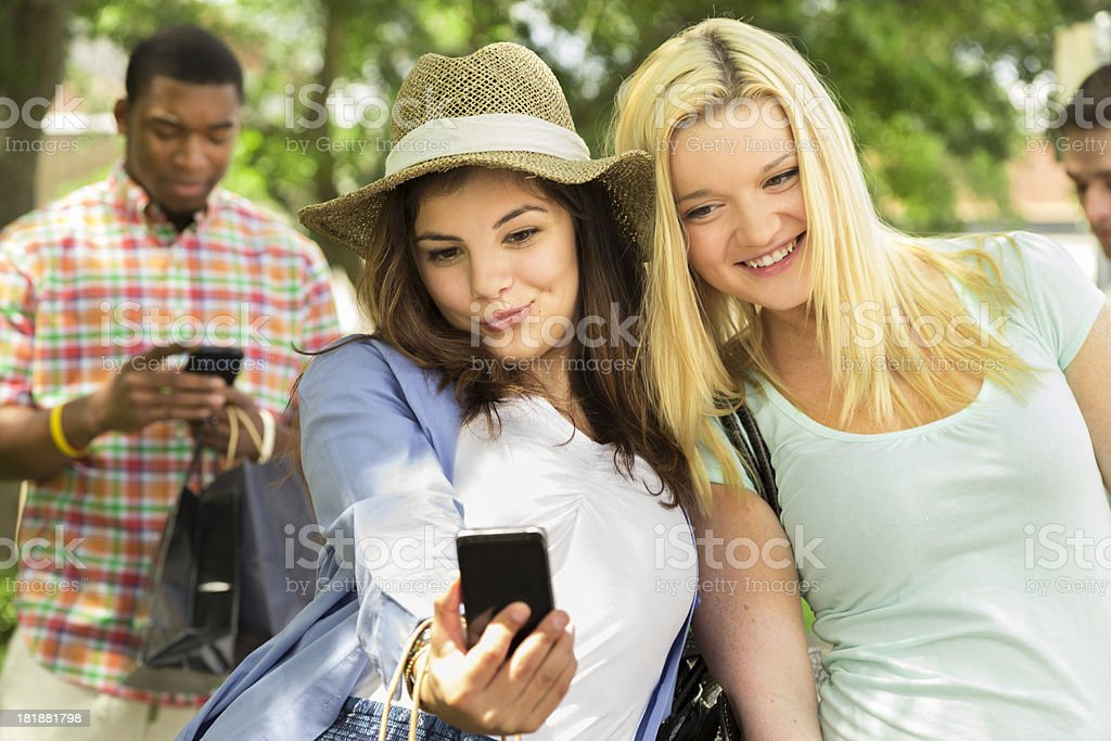 Technology:  Young adults and teens posing for cell phone camera royalty-free stock photo